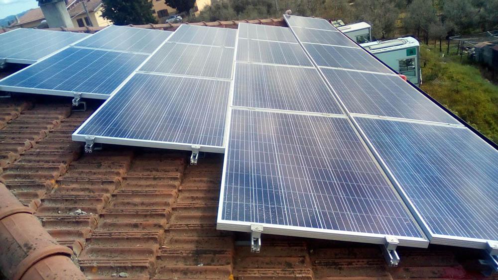 Fotovoltaico, casa con tetto e impianto fotovoltaico e famiglia con padre madre e bambino