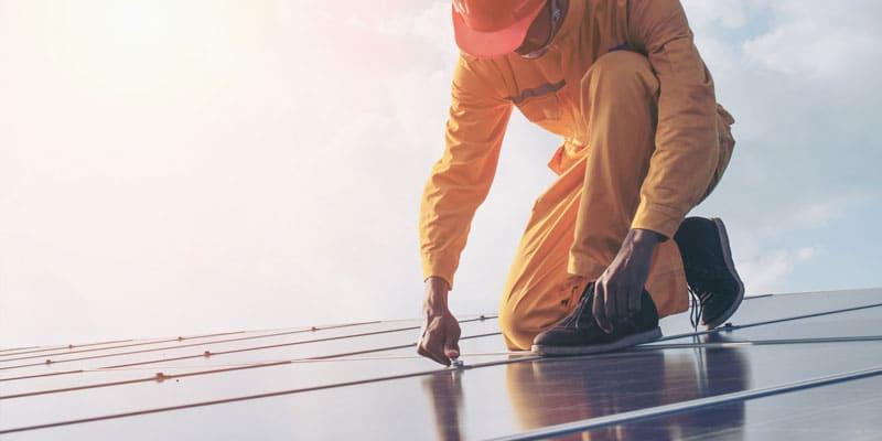 Pannello solare applicato sul tetto da un lavoratore Works