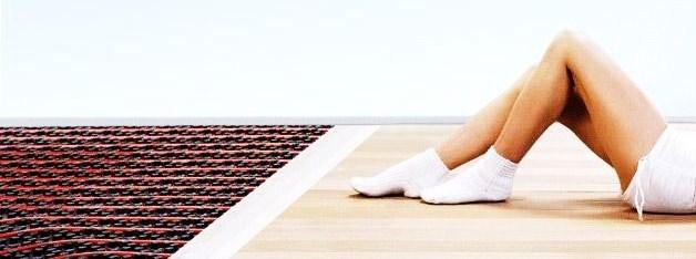 Impianti a pavimento in abitazione con bambini che giocano e genitori sul divano
